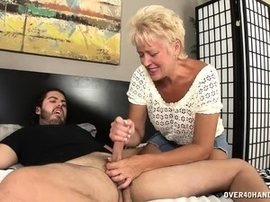 Aunt Tracy's skillful hands slowly bring a hung stud's cock to orgasm