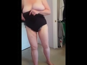 squeezing her bbw body, big tits into black girdle